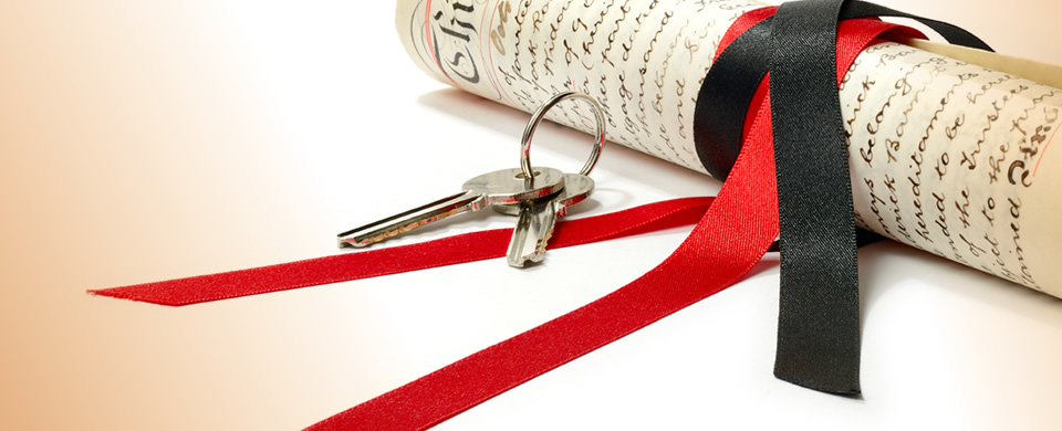 Legal Documents tied with red ribbon and keys to a property